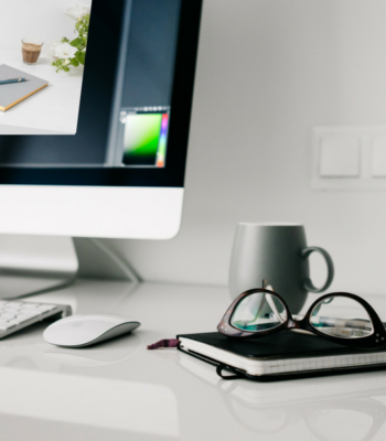 White Desk with Mac Notebook and Glasses